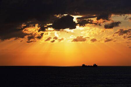 Golden hour above baltic sea and silhouette of cargo ship on horizon Standard-Bild