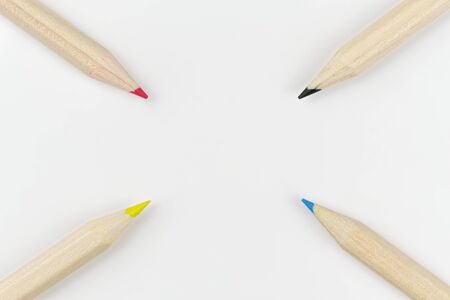 Four colored pencils on a white background arranged as a target