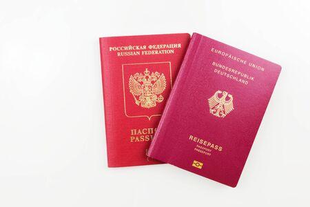 Original Russian passport behind German passport isolated on white background