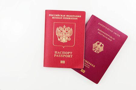 Original German passport behind Russian passport isolated on white background