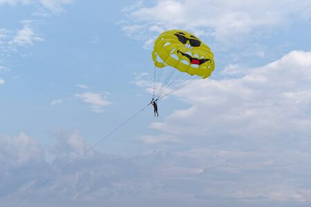 Parasailing, single person hanging under parachute against blue cloudy sky