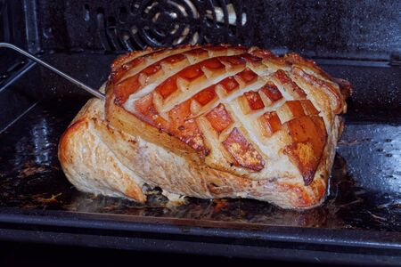 Close-up of roast pork with crackling in the oven