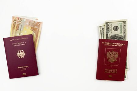 Official German and Russian passports with american dollars an euro banknotes on white background