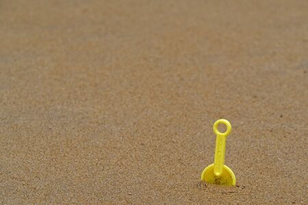 High angle view of plastic children toy shovel in the sand. Concept of beach recreation for children. Space for text, copy space