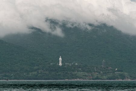 Clouds rolling over the mountain range and Linh Ung pagoda of Son Tra Peninsula. Da Nang in Central Vietnam