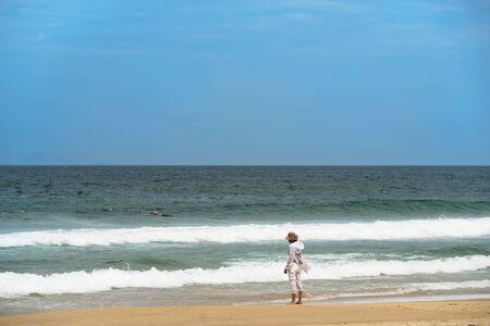Woman in white jacket relaxing on the beach, Da Nang, Vietnam
