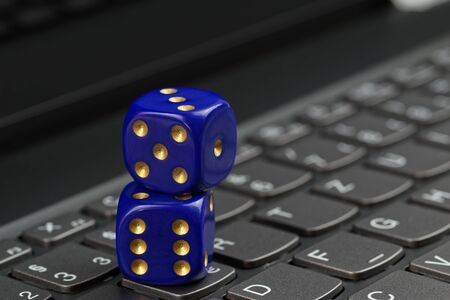 Concept photo of two blue dices on black computer keyboard Standard-Bild