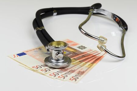 High angle view of stethoscope and euro banknotes on white background