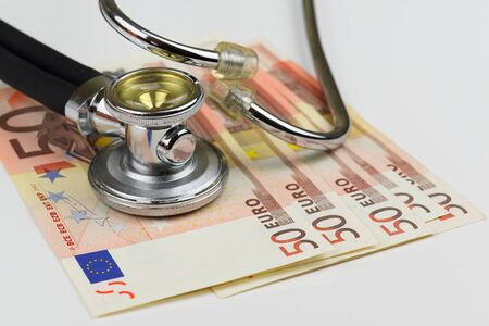 Close-up view of stethoscope and euro banknotes on white background