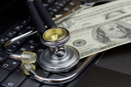 High angle view of stethoscope and american dollars on black computer keyboard