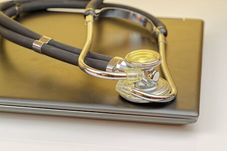 High angle view of stethoscope lying on closed notebook