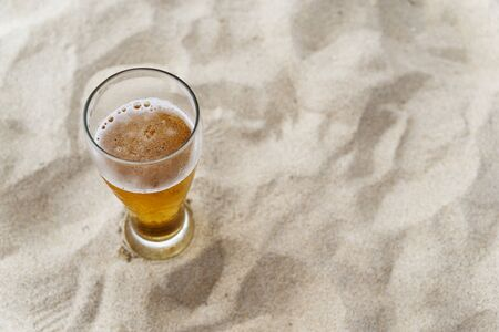 Vacation concept. High angle view of beer glass in a sand