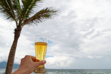 Vacation concept. Male hand holding glass of beer on the beach against cloudy sky