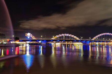 Panoramic view of illuminated Dragon bridge at night. Da Nang, Vietnam