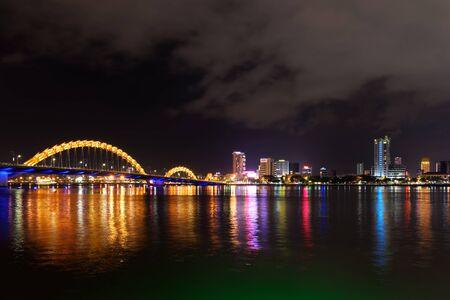 Night view of illuminated Dragon bridge over the han river and buildings in DaNang city, Vietnam