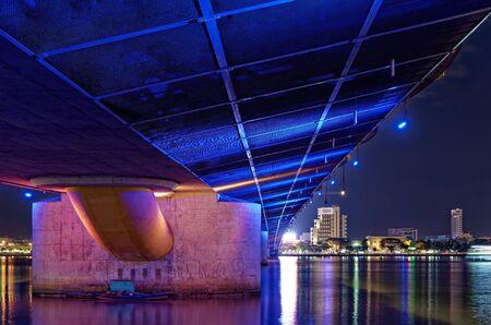 Colorful illumination under the bridge at night. Low angle view of Dragon bridge construction from directly below. Da Nang, Vietnam