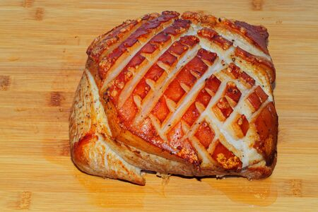 Pork roast with crackling on wooden board, ready to eat