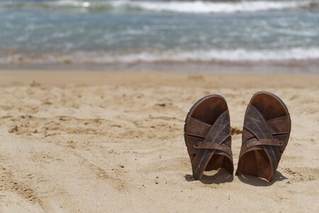 Vacation concept. Sandal shoes in a sand on the beach against sea