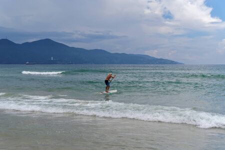 Da Nang, Vietnam - May 12, 2019: Man with fair hair stand up paddles on the seashore against mountain and cloudy sky Standard-Bild
