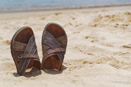 Vacation concept. Close-up of sandal shoes in a sand on the beach
