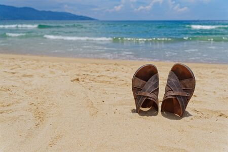 Vacation concept. Sandal shoes in a sand on the seashore against horizon and sky