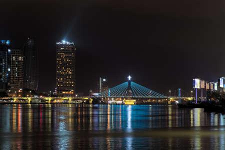Da Nang, Vietnam - May 11, 2019: Illuminated skyscrapers and Han river bridge at night