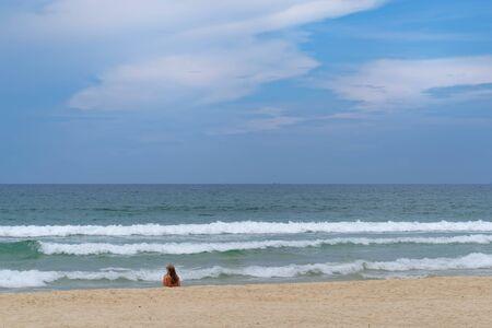 Panoramic view of woman sitting on seashore and looking toward horizon over water. Da Nang, Vietnam