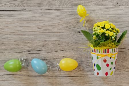 Easter decoration. Yellow flowers in decorative pot and three colorful eggs on wooden background Standard-Bild - 143779589