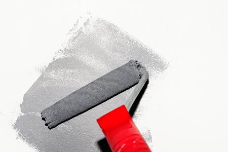 Paint roller with gray stroke on white wall Standard-Bild