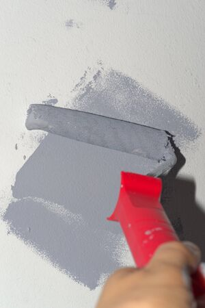 Human hand holding paint roller with gray stroke on white wall