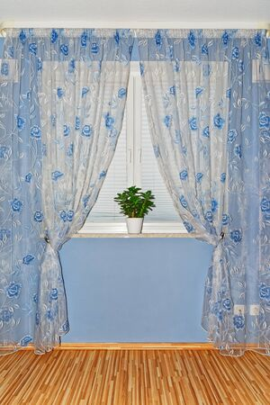 Curtain interior decoration in a room with blue wall Standard-Bild