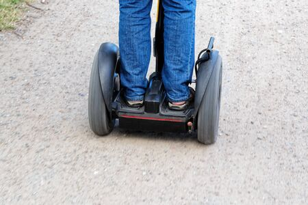 Rear view of man riding electric gyropode - two-wheeled, self-balancing board