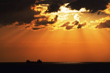 Golden hour above baltic sea and silhouette of cargo ship on horizon Standard-Bild