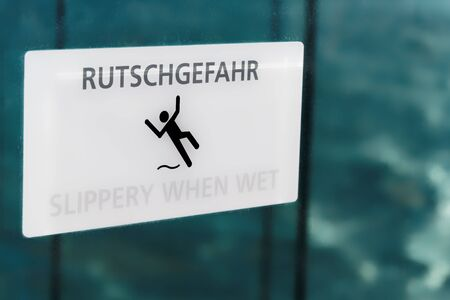 White slippery when wet sign with warning in German and English Standard-Bild - 149191694