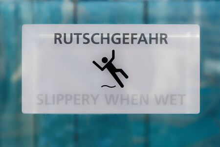 White slippery when wet sign with warning in German and English