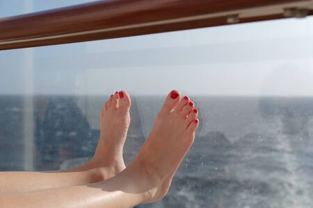 Close-up of woman feet at the glass railing of cruise ship