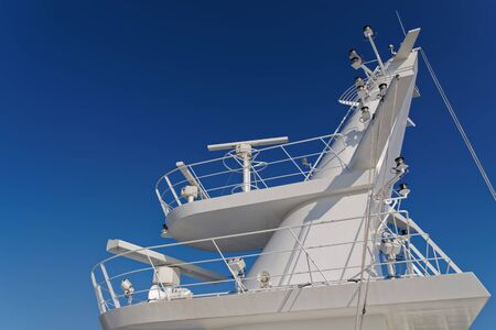 White mast of modern ship against clear blue sky
