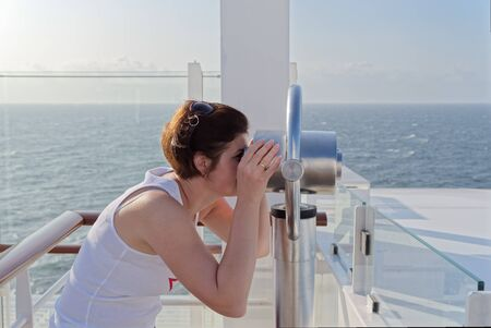 Side view of young woman in white shirt looking through an observation telescope on a ship Standard-Bild