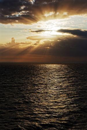 Beautiful sunset scene of sun rays shining through clouds over the sea