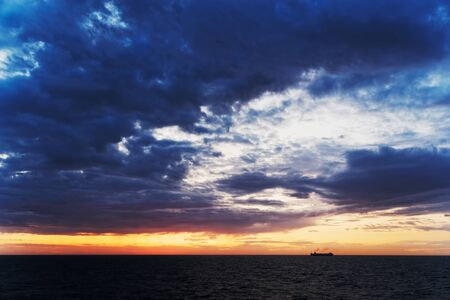 Beautiful scene of dark blue clouds above sea and ship silhouette at horizon during sunset