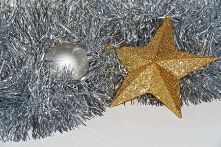 Christmas decoration on white background, silver colored bauble and golden star lying in a tinsel Standard-Bild