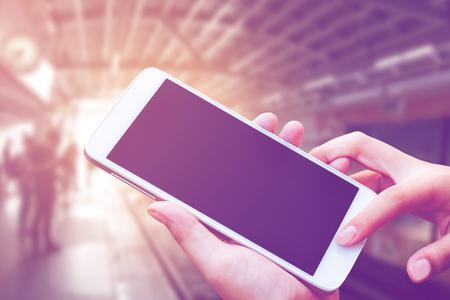 vrouw de hand te houden en touch screen smart phone, tablet, mobiele telefoon over de stad metro station in de ochtend achtergrond, vintage filter kleurtoon.