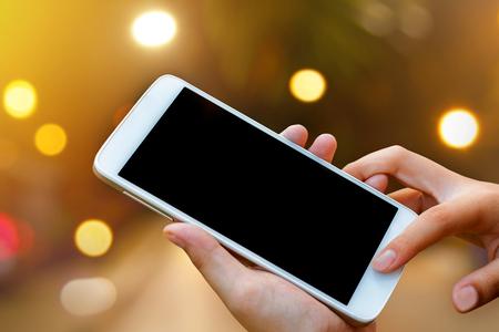 ženská ruka držet a dotykový displej chytrý telefon, tablet, mobil na abstraktní rozmazané bokeh městské noci světlé pozadí pozadí.