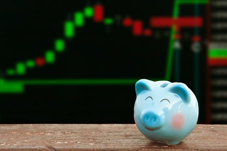 blue piggy bank on wooden table over share of stock; share of business background,money and saving concept.