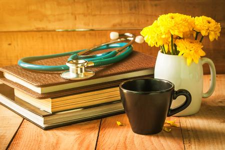 selectieve aandacht van lege kopje koffie op een houten vloer met gele bloemen in witte pot en stethoscoop op boeken, 's morgens zonlicht. vintage kleurtoon.
