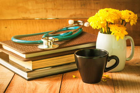 selective focus of empty cup of coffee on wooden floor with yellow flower in white pot and stethoscope on books , morning sunlight. vintage color tone.
