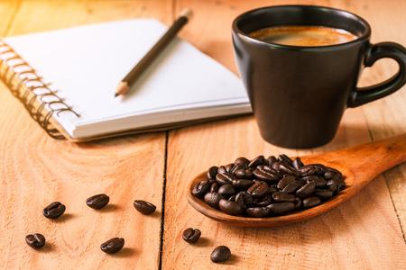 selectieve aandacht van koffiebonen op houten lepel met een notebook en een kopje espresso, vintage kleurtoon. Stockfoto