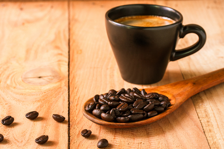 selective focus of coffee beans on wooden spoon with notebook and cup of espresso ,vintage color tone.