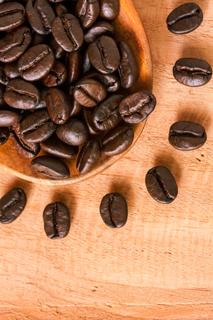 selective focus of coffee beans on wooden spoon
