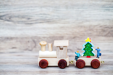 Miniature Figure Toy Wooden Train carry Christmas tree on wooden background, Image for Christmas Holiday decorative concept.
